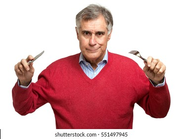Senior man holding a fork and a knife isolated on a white background