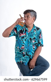 The senior man holding glass of whiskey and cigarette, sitting on a chair and look to the right side on white background