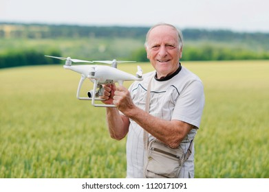 Senior man holding hand-tossed white quadcopter over green fields background. Operation of drone in air for profession aerial video and photo
