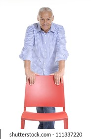Senior man holding a red chair on white background.