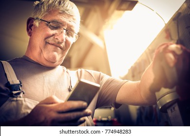 Senior Man holding smart pone and typing messages. Close up.