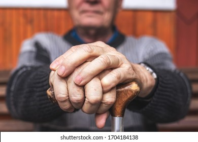 Senior man holding walking cane in his hand. Old pensioner sitting on bench and relaxing. Aging process and disability problem