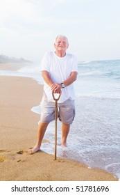 senior man holding a walking cane on beach