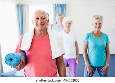 Senior man holding yoga mat during sports class
