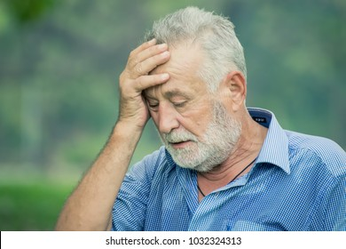 senior man holds his head in despair.Senior man touches his forehead.businessman has headache and health from overworked. tired concept.
