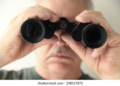 A senior man holds an old pair of binoculars pointed at the camera.