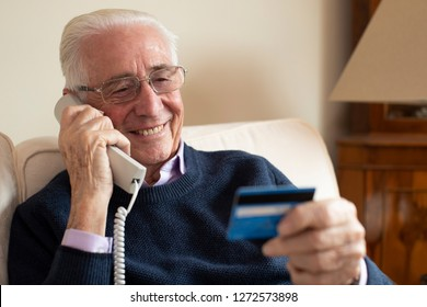 Senior Man At Home Giving Credit Card Details On The Phone