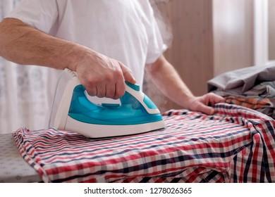 Senior man at home ironing his clothes