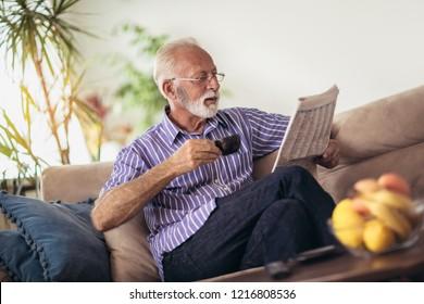 Senior man at home reading newspaper