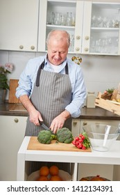 Senior man as homemaker preparing healthy vegetable dish