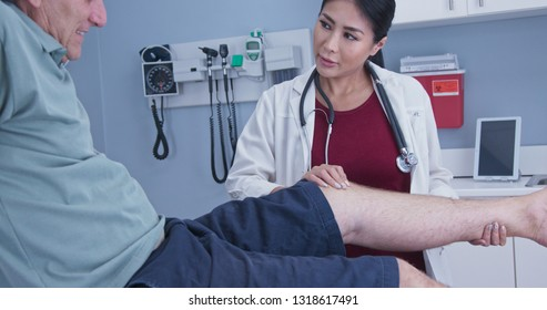 Senior man with hurt knee getting it checked by female medical professional. Physical therapist or doctor with older male patient in exam room checking range of motion on knee injury