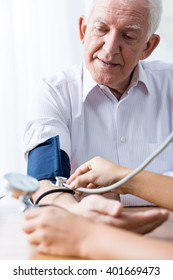 Senior man with hypertension having regular blood pressure control