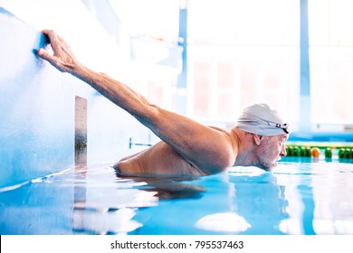 Senior man in an indoor swimming pool.
