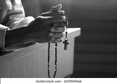 Senior man kneel, holding wooden rosary beads in hands with Jesus Christ holy cross crucifix in the church. Natural light background. Prayer pose crop closeup in black and white. Catholic symbol.