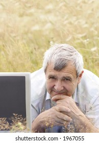 Senior man with laptop on the meadow
