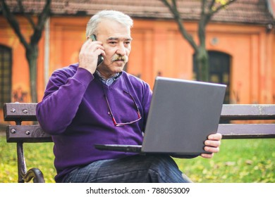 Senior man with laptop in park talking on mobile phone.