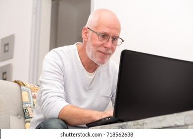 a senior man with laptop sitting in sofa