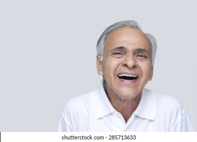 Senior man laughing over white background