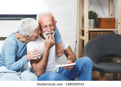 Senior man laughing while take medication for potency while his wife smile too. Elderly couple in bedroom.