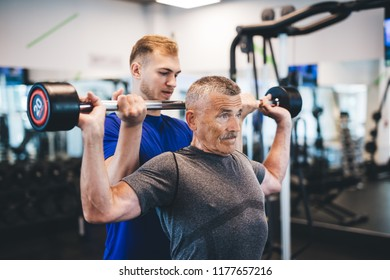 Senior man lifting weights with help of gym assistant. Work of personal trainer. Bodybuilding.