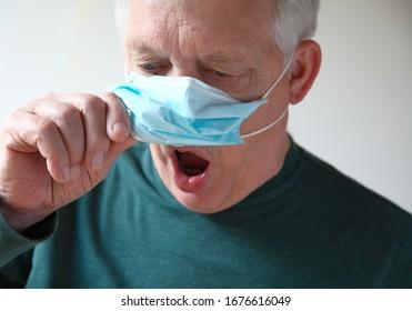 Senior man lifts his medical mask to gasp for air