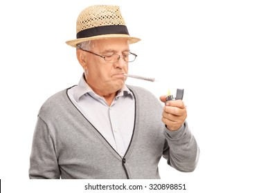 Senior man lighting up a joint with a gray lighter isolated on white background