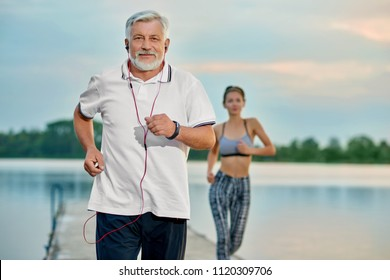 Senior man listening music, running near lake in evening. Young girl running behind. Outdoor activities, healthy lifestyle, strong bodies, fit figures. Different generations. Sport, yoga, fitness
