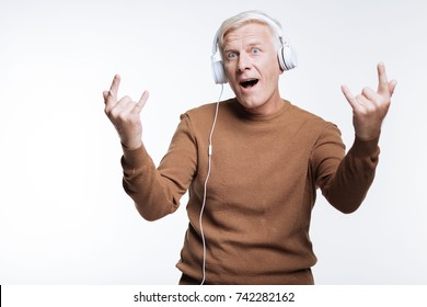 Senior man listening to music and showing sign of horns