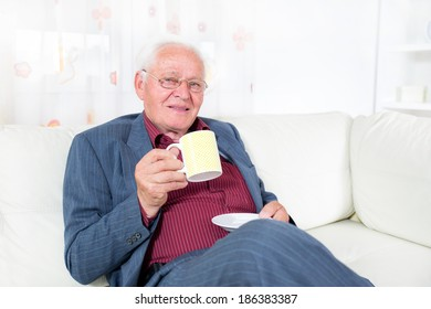 Senior man in living room with coffee