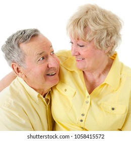 A senior man looking adoringly into his wife's eyes.  On a white background.