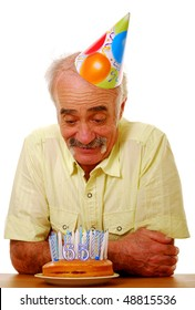 Senior man looking at birthday cake and happy to be 65