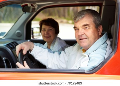 Senior man looking at camera in the car with his wife on background