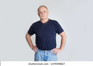 senior man looking at camera on gray background