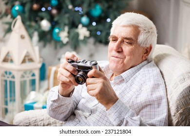 Senior man looking at display of retro style camera and smiling against Christmas background