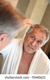 Senior man looking at hair in mirror