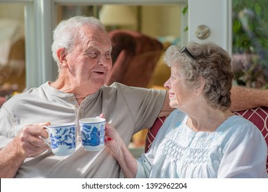 Senior man looking at his wife. A beautiful senior couple in their seventies talks and laughs while they enjoy coffee or tea on their sunny porch one morning.