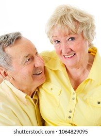 A senior man looking lovingly at his wife while she smiles at the viewer.  On a white background.