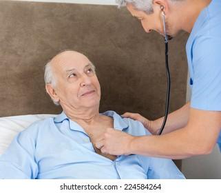 Senior man looking at male caretaker examining him with stethoscope at nursing home
