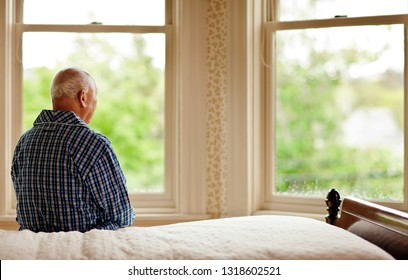 Senior man looking out his bedroom window while sitting on a bed in his pajamas.