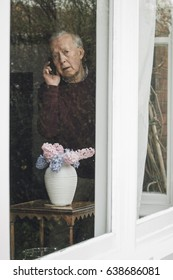 Senior man is looking out from his window into the street and is reporting a neighborhood crime on the phone.