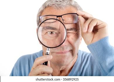 Senior man looking through magnifying glass. Focus on magnifiying glass.