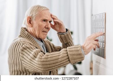 senior man looking at wall calendar and touching head