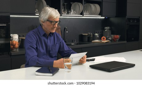 Senior man looks at closed letters in the kitchen