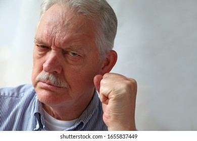 Senior man looks hostile and gestures with copy space