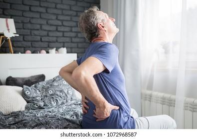 Senior Mann mit Rückenschmerzen im Bett