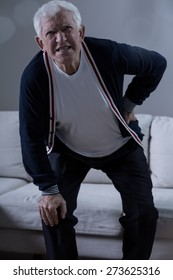 Senior man with lumbar pain holding his back