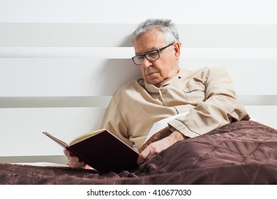 Senior man is lying in bed and reading a book before sleep