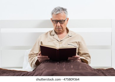 Senior man is lying in bed and reading a book before sleep.