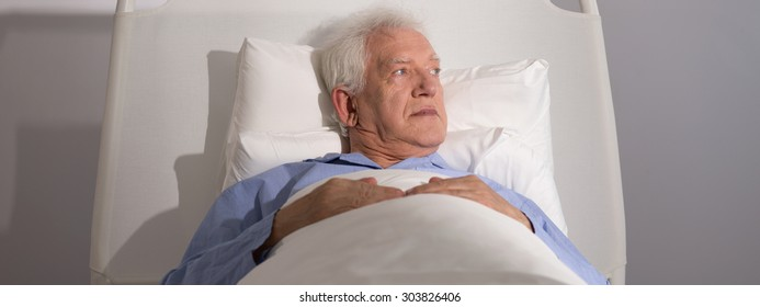 Senior man lying in hospital bed - panorama