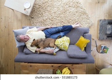 Senior man is lying on the sofa in the living room of his home. He has his dog lying on him who is also asleep.